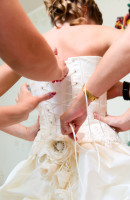 bride friends are helping to dress her before wedding